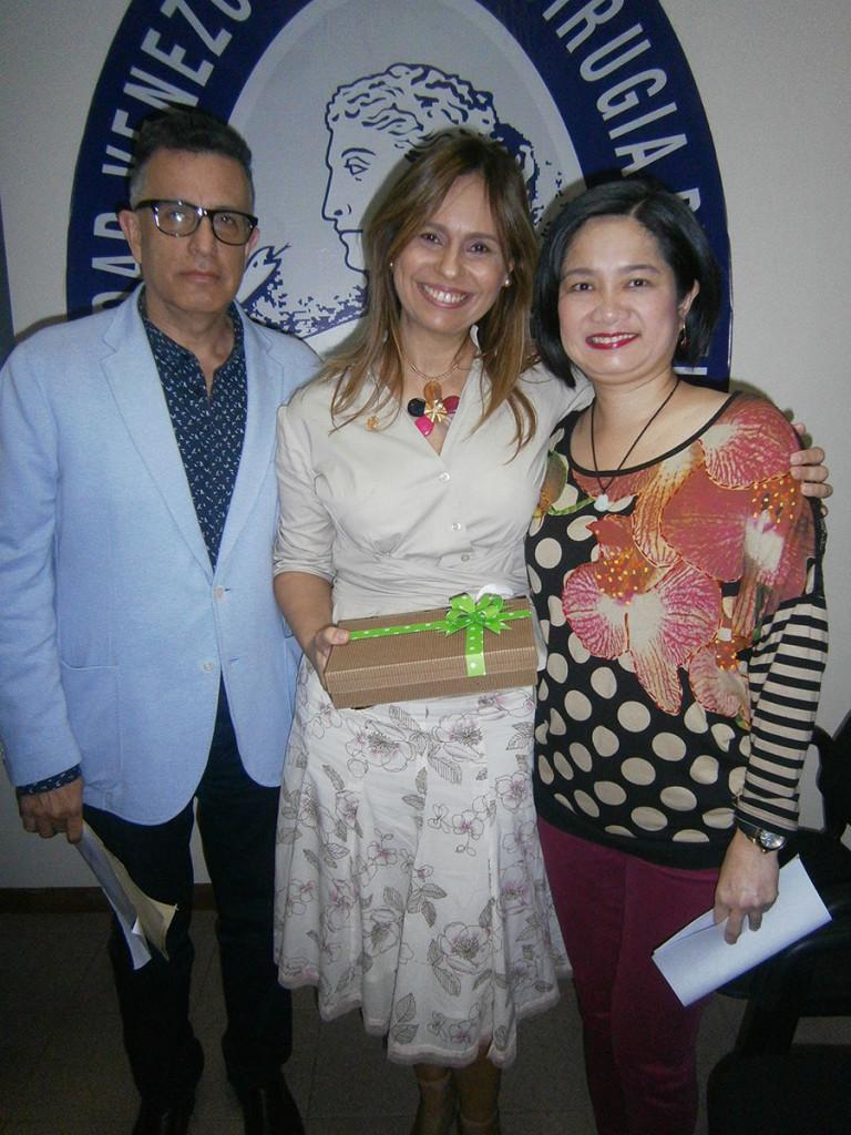 El Dr. Edgar Martínez y la Dra. Gladys Chow, entregando un obsequio a la Dra. María Rosario Fermín